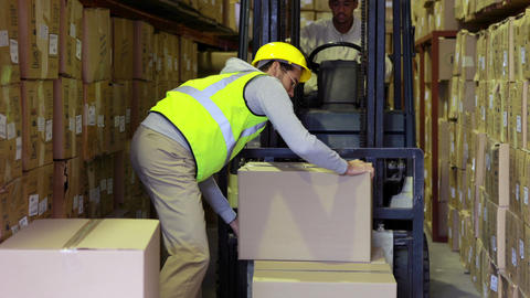 Warehouse worker packing boxes on forklift Footage