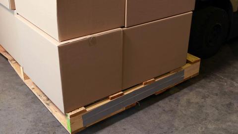 Forklift picking up palette of boxes Live Action