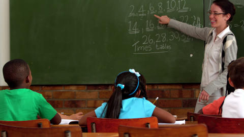 Young teacher teaching math to young class in classroom Footage