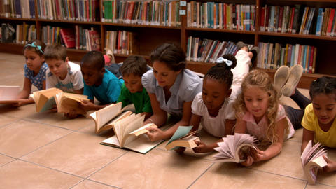 Teacher and pupils reading books on library floor Footage