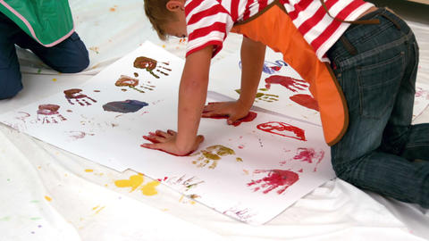 Cute little boys painting lying on paper in classroom Footage