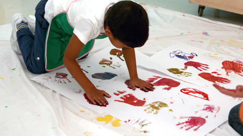 Cute little boys painting with hands lying on paper in classroom Footage