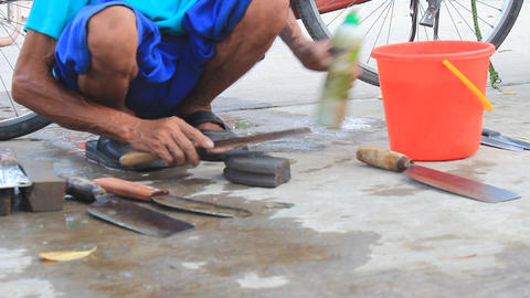 A blacksmith sharpens a knife for customer in the market, Asia Footage
