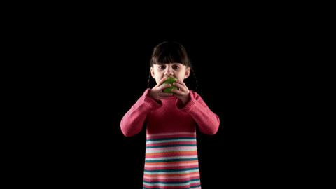 girl eating apple on black background Footage