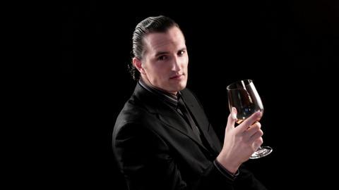 businessman drinking wine on black background Footage