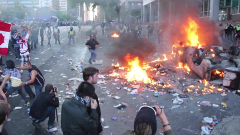 Man running over burning debris at riot - HD Footage