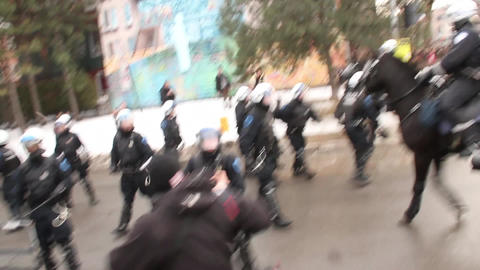 Riot officer uses baton to push away protesters -  Footage