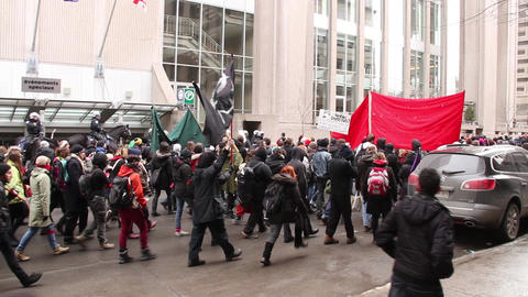 Crowd of protesters with flags walk down downtown  Footage