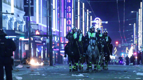 Riot officers on horses patrolling chaotic street Footage