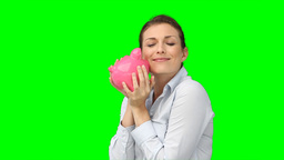 A smiling woman kissing her piggybank Footage