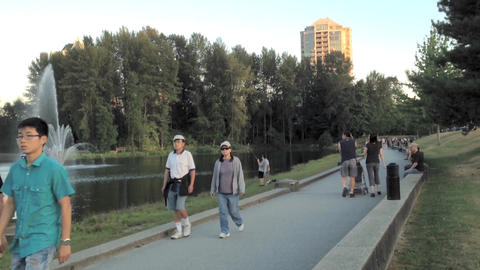 People walk in the park next to a lake Footage