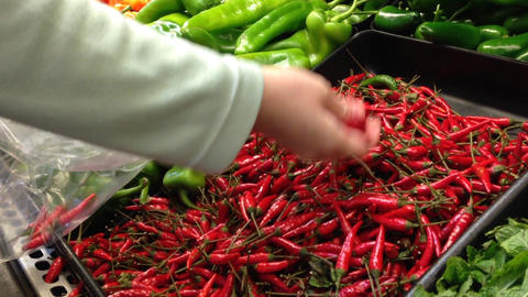 Woman Selecting Fresh Hot Chili Pepper In Grocery  stock footage
