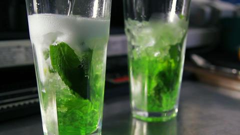 Barman pouring lemonade into glass with ice, lemon Footage