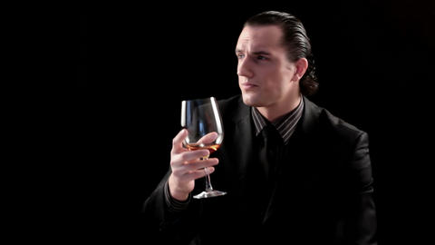 businessman drinking wine on black background Footage