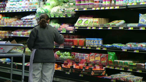 Woman Stocking Tomatoes In Produce Footage