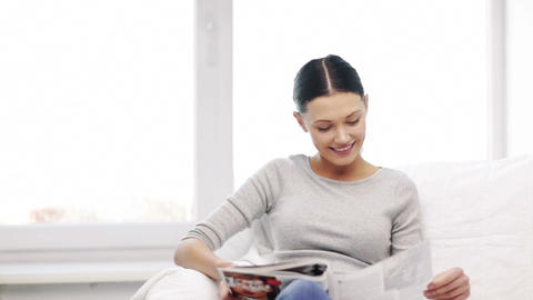 smiling woman reading magazine at home Footage