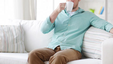 man sitting and drinking from a cup at home Footage