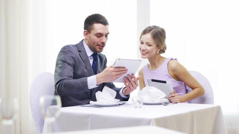 couple with menus on tablet pc at restaurant Footage