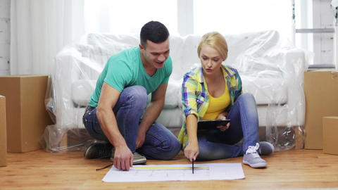 smiling couple looking at blueprint in new home Footage