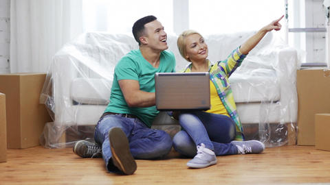 couple with laptop sitting on floor in new house Footage
