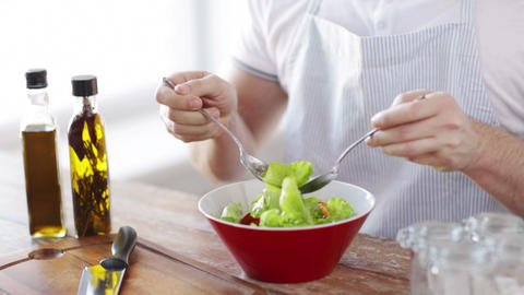 close of male hands mixing salad in a bowl Footage