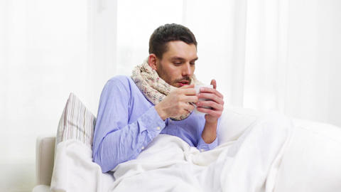 ill man with flu drinking hot tea at home Footage