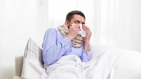 ill man with flu at home sneezing and blowing nose Footage