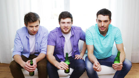happy male friends with beer watching tv at home Footage