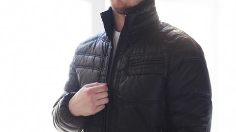 close up of man unzipping his black jacket at home Footage