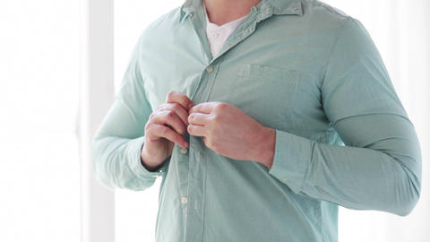 close up of man buttoning his shirt at home Footage
