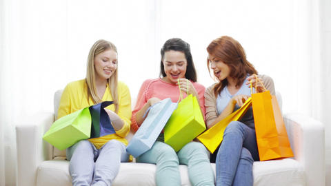 smiling teenage girls with many shopping bags Footage