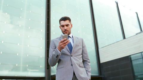 serious businessman with smartphone outdoors Footage
