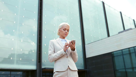 serious businesswoman with smartphone outdoors Footage