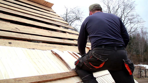 Roofer nailing the wooden roof tiles on the cedar  Footage