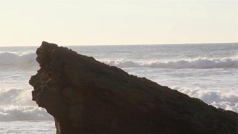 Big stone on the beach splashing on big rocks Live Action