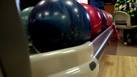 Multi-colored bowling balls rolling Footage
