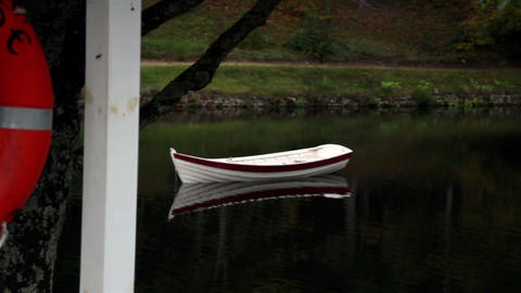 Row boat floating and an orange life preserver Footage