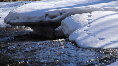 A snow-covered area with flowing water underneath Footage