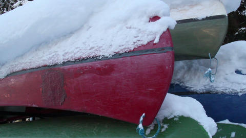 Four boats turned upside down are covered with sno Footage