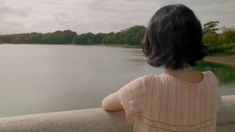 A young woman stands looking at the lake alone ビデオ