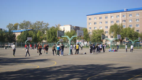 Chinese students play basketball outdoors Live Action
