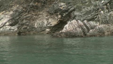 The waves lapp against rocky coastline Footage