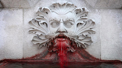 a statue of a man's head vomiting blood Live Action