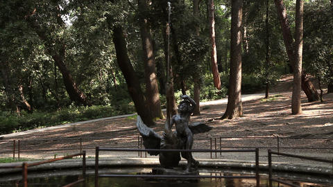 a statue in the forest near water Live Action
