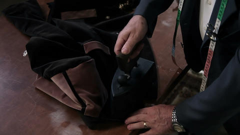 Close up shot of the tailors hands, ironing a fabr Live Action