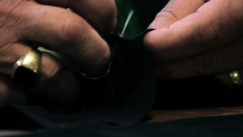 Close up shot of a tailor sewing a button Live Action