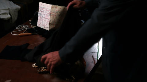 Close up shot of the tailors hands, cutting a fabr Live Action