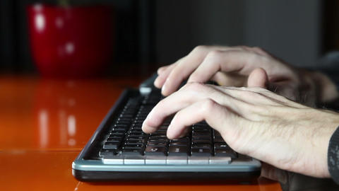 man`s hands typing on a computer keyboard Footage