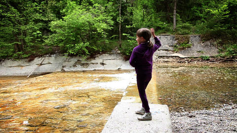 Shot of little girl throwing stones in river Live Action