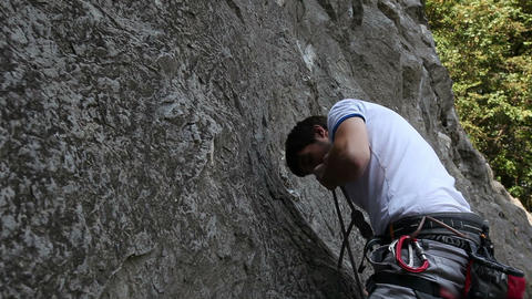 Young man rock climbing on a natural rock Live Action
